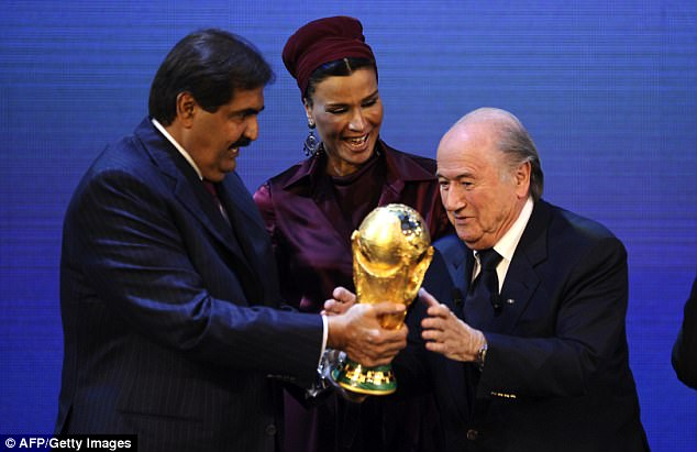 Ex-FIFA president Sepp Blatter hands the World Cup trophy to the Emir of Qatar and his wife. Source: AFP/Getty Images.
