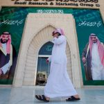 A man speaks on the phone as he walks past posters depicting Saudi Arabia's King Salman