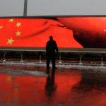 Человек на фоне экрана с китайским флагом, исключили из Компартии за коррупцию