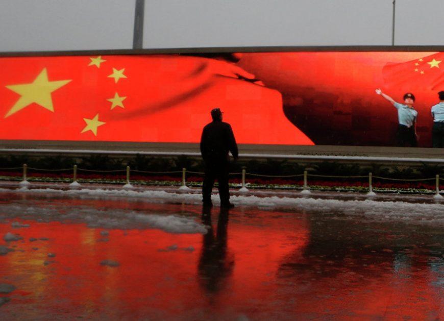Человек на фоне экрана с китайским флагом