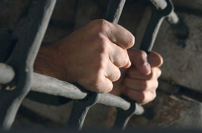 Руки заключенного держатся за прутья решетки