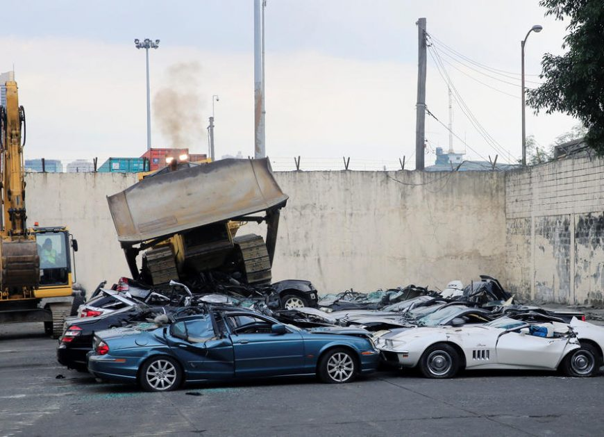A bulldozer destroys condemned smuggled luxury cars worth 61,626,000.00 pesos during the 116th Bureau of Customs