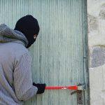Мужчина в маске взламывает дверь ломом