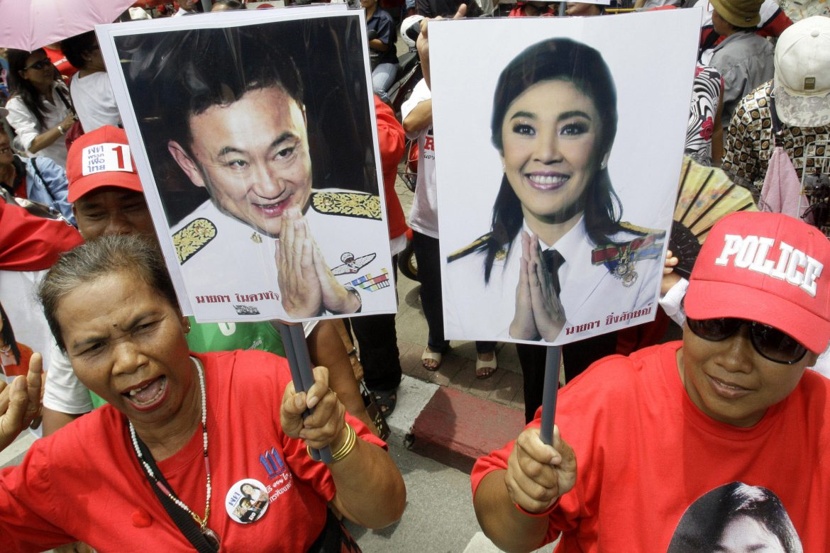 экс-премьеры Таиланда, Supporters of Pheu Thai Party, holding portraits of former Thai Prime Minister Thaksin Shinawatra, left, and his sister Yingluck Shinawatra, cheer up outside Parliament in Bangkok, Thailand, on Friday, Aug. 5, 2011. Thai lawmakers chose U.S.-educated businesswoman Yingluck as the country's first female prime minister Friday, setting the stage for the 44-year-old political novice to take charge of a volatile nation that's been deeply divided since her brother was ousted in a 2006 coup.