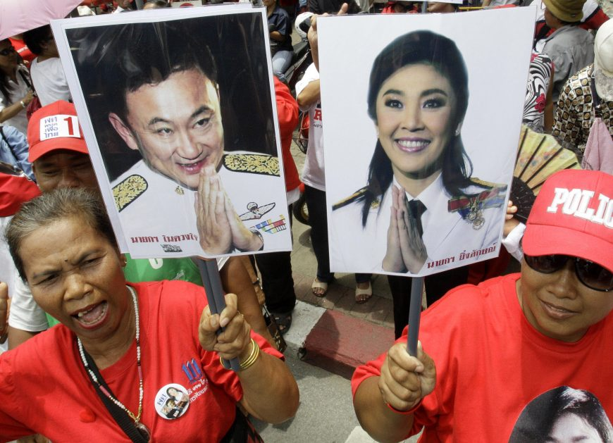 Supporters of Pheu Thai Party, holding portraits of former Thai Prime Minister Thaksin Shinawatra, left, and his sister Yingluck Shinawatra, cheer up outside Parliament in Bangkok, Thailand, on Friday, Aug. 5, 2011. Thai lawmakers chose U.S.-educated businesswoman Yingluck as the country's first female prime minister Friday, setting the stage for the 44-year-old political novice to take charge of a volatile nation that's been deeply divided since her brother was ousted in a 2006 coup.