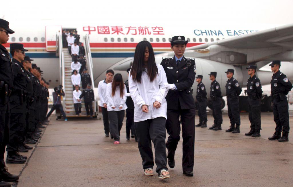 Подозреваемые в мошенничестве репатриированы в Китай, полицейские сопровождают их из самолёта в служебные автомобили