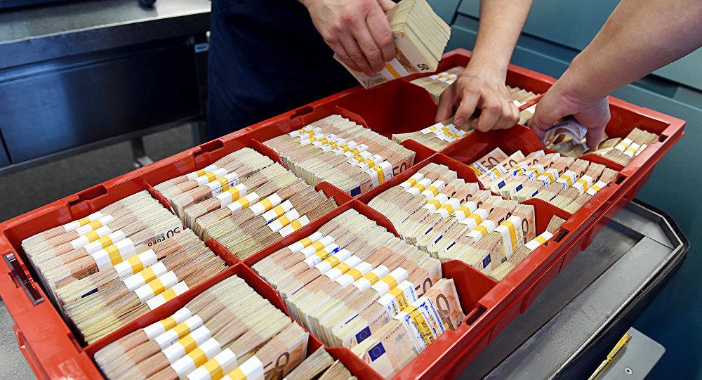 Люди изымают евро в купюрах номиналом 500, упакованные в пачки. Вывели